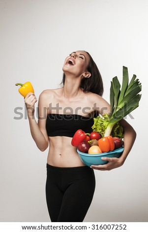 Portrait of woman promoting healthy eating. Beautiful young brunette woman with slim body holding bowl with fruits and vegetables. Healthy eating lifestyle and weight loss concept.  Studio background. - stock photo