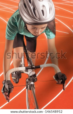 portrait of  woman riding race bike on a track. model equipped with a professional biking gear, uses professional race bike. vertical shot. composite image