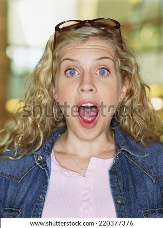 Portrait of woman screaming with mouth wide open - stock photo