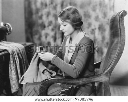 Portrait of woman sewing - stock photo
