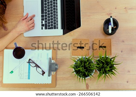 Portrait of  woman sitting at  desk with a laptop - stock photo