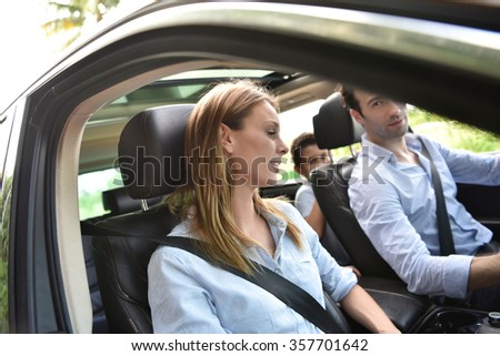 Portrait of woman sitting in car with family - stock photo