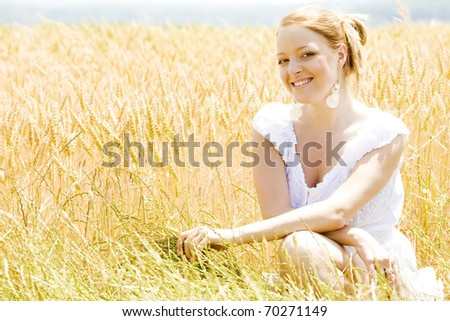 portrait of woman sitting in grain field - stock photo