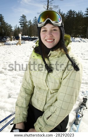 Portrait of woman skier at bottom of the hill kneeling in snow