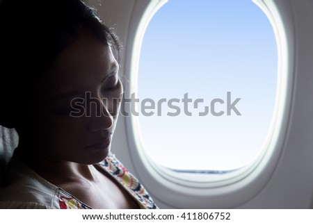 Portrait of woman sleeping in an airplane beside window. Tired passenger relaxes in a flying aircraft.