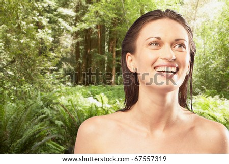 Portrait of woman smiling in forest - stock photo