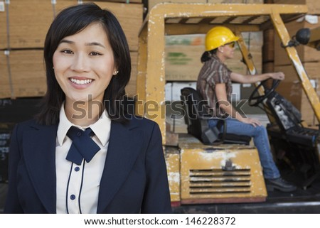 Portrait of woman smiling while female industrial worker driving forklift truck in background - stock photo