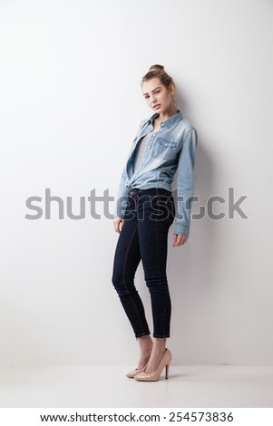 Portrait of woman standing against wall. Isolated over grey background. - stock photo