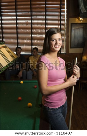 Portrait of woman standing by billiards table holding pool stick. - stock photo