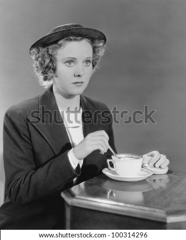 Portrait of woman stirring beverage - stock photo
