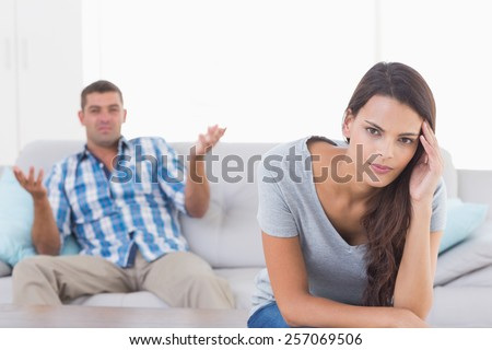 Portrait of woman suffering from headache while man quarreling at home - stock photo