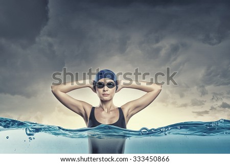 Portrait of woman swimmer in cap and glasses - stock photo