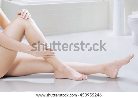 Portrait of woman take care of her legs while sitting on the floor at bathroom