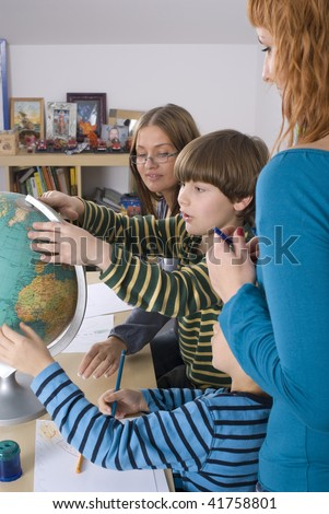 Portrait of woman teaching children in a classroom - stock photo