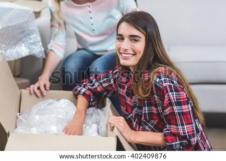 Portrait of woman unpacking carton boxes in their new house - stock photo
