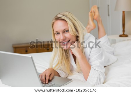 Portrait of woman using laptop while lying in bed at home