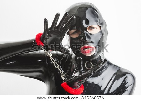 portrait of woman wearing latex clothes with handcuffs - stock photo