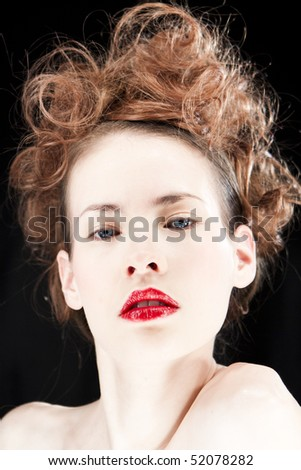 Portrait of woman wearing red lipstick isolated against a black background.