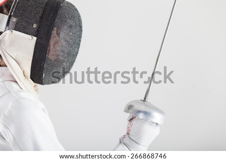 Portrait of woman wearing white fencing costume practicing with the sword - stock photo