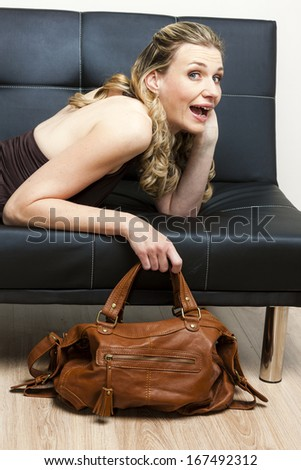 portrait of woman with a handbag lying on sofa