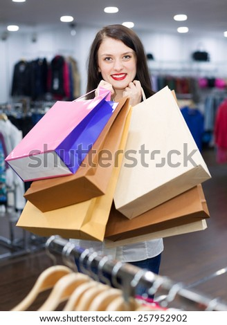 Portrait of woman with a lot of shopping bags at fashionable store - stock photo