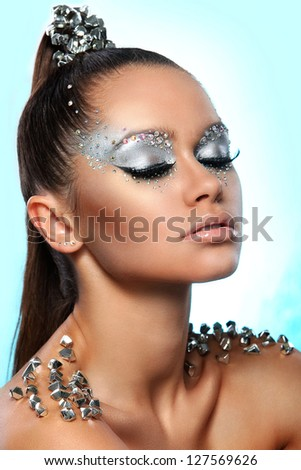 Portrait of woman with artistic make-up and rhinestones over background