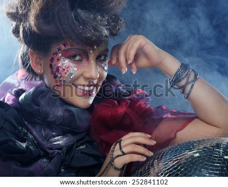 portrait of woman with artistic make-up in blue smoke - stock photo