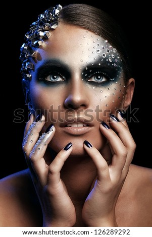 Portrait of woman with artistic make-up isolated over black background