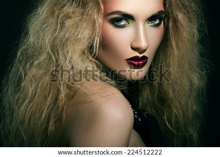 Portrait of woman with curly hair on green background - stock photo