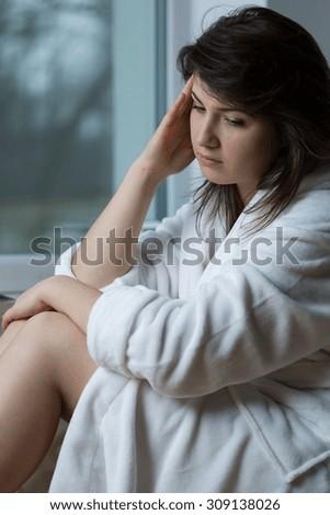 Portrait of woman with depression having headache - stock photo
