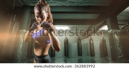 Portrait of woman with fighting stance against red boxing area with punching bags - stock photo