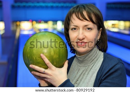 Portrait of woman with green ball for bowling