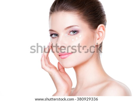 Portrait of woman with healthy face applying cosmetic cream under the eyes. - stock photo