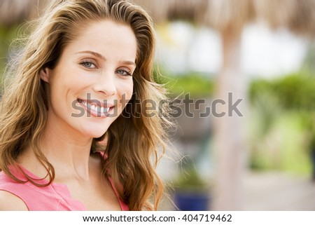 Portrait of woman with long brown hair outdoors - stock photo