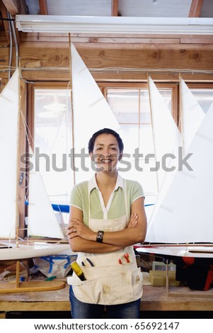 Portrait of woman with model sailboats