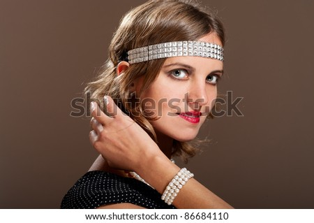 Portrait of woman with pearl bracelet fixing her hair