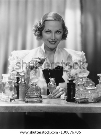 Portrait of woman with perfume bottles - stock photo