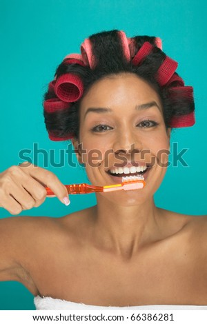 Portrait of woman with rollers in hair brushing teeth - stock photo