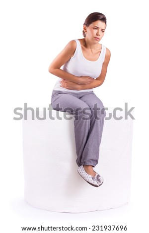 Portrait of woman with stomach ache sitting on a roll of toilet paper, her hands on abdomen - stock photo