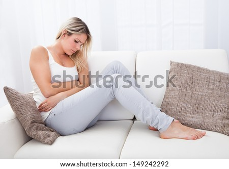 Portrait of woman with stomach ache sitting sofa - stock photo