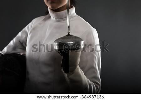 Portrait of woman with the sword, wearing white fencing costume. - stock photo