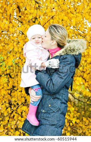 portrait of woman with toddler in autumnal nature - stock photo