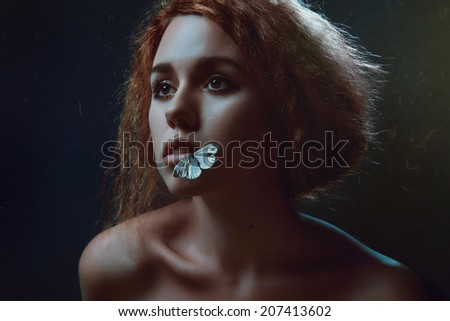 Portrait of woman with white butterflies in studio - stock photo
