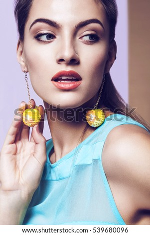 Portrait of woman with yellow earrings and blue dress on multi background