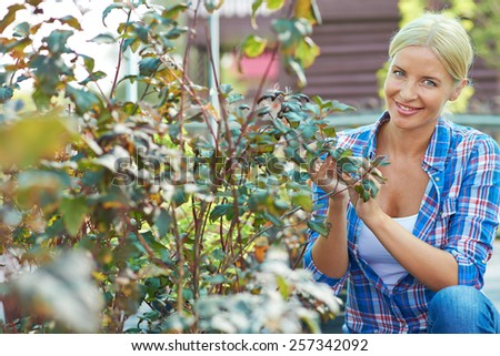 Portrait of woman working in the garden - stock photo