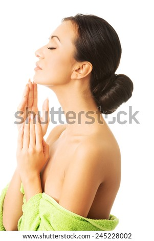 Portrait of woman wrapped in green towel touching her neck - stock photo