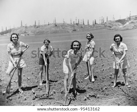 Portrait of women digging in field - stock photo