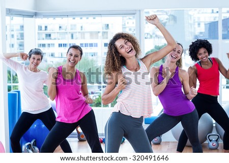 Portrait of women exercising with clasped hands in fitness studio
