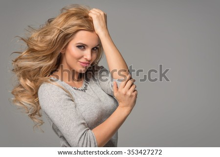 Portrait of wonderful young blonde woman with long hair looking at camera, smiling.  - stock photo