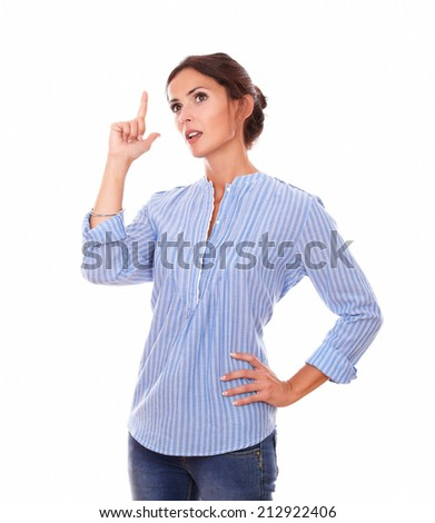 Portrait of wondering adult lady on blue blouse looking up and pointing up her finger while standing on isolated white background - copyspace - stock photo